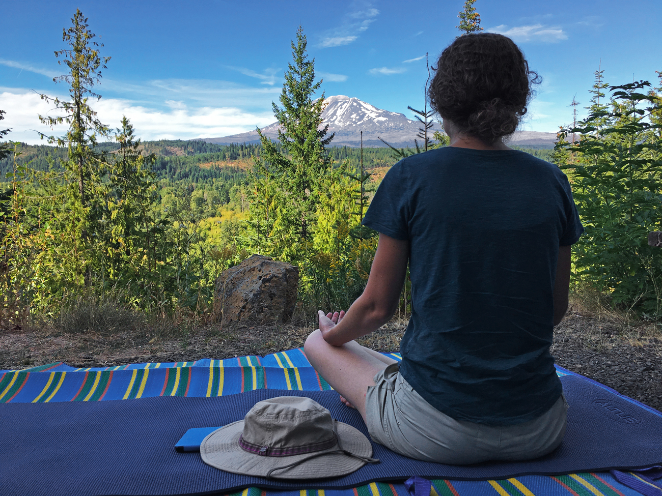Christina meditating on her yoga mat with a view of Mt. Adams
