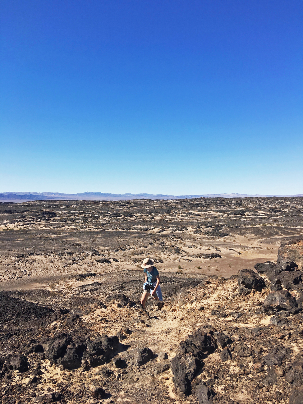 Christina on the trail to Amboy Crater surrounded by sand and an extensive field of black lava rock