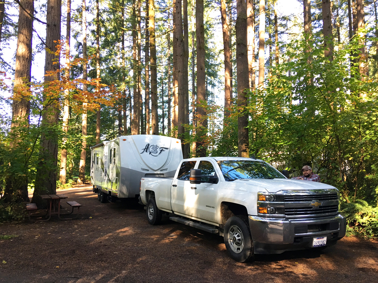 Michael standing with our truck and trailer under tall firs at Big Fir Campground and RV Park