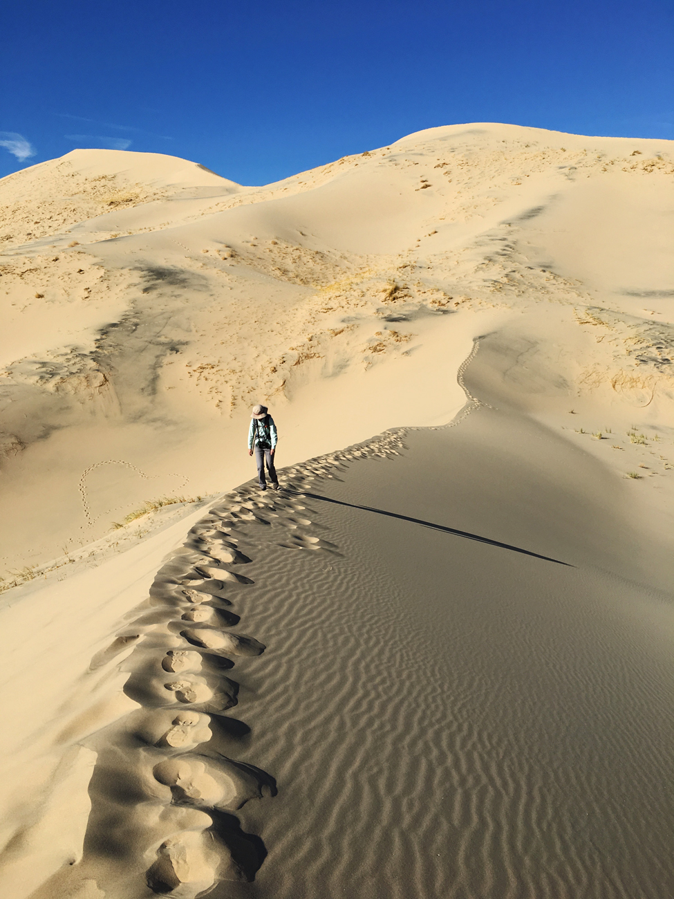 Christina slogging through the sand on the peak of one of the dunes