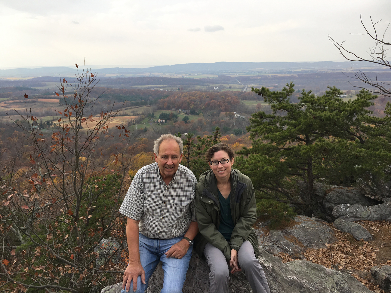 Christina and her dad sitting on a large white rock on top of Sugarloaf Mountain with a view of southern Frederick County