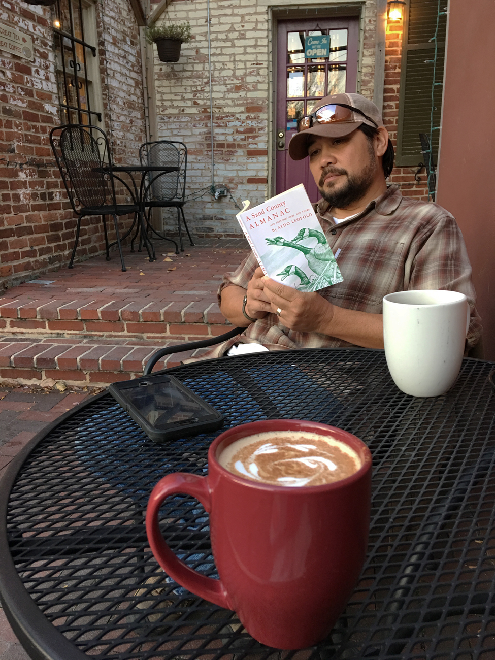 Michael reading at an outdoor table with mugs of coffee and tea on the table in Frederick