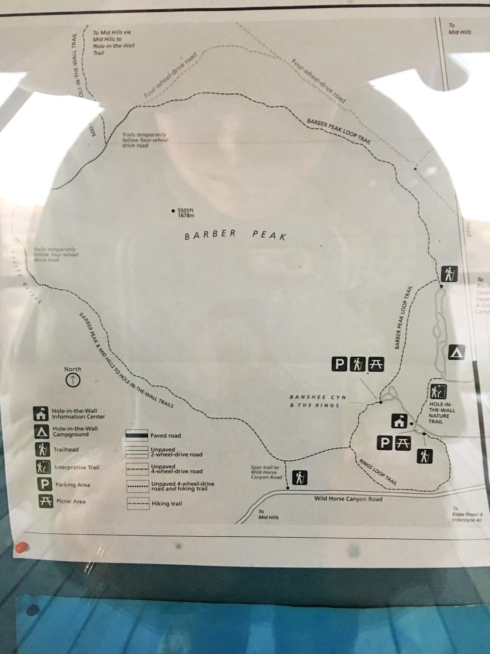 Christina's reflection on a sign of the Barber Peak Loop Trail map