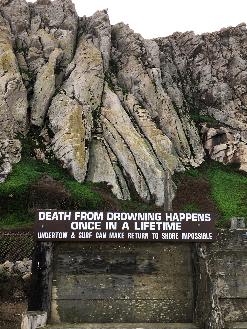 """Sign """"Death from drowning happens once in a lifetime"""" at Morro Rock"""