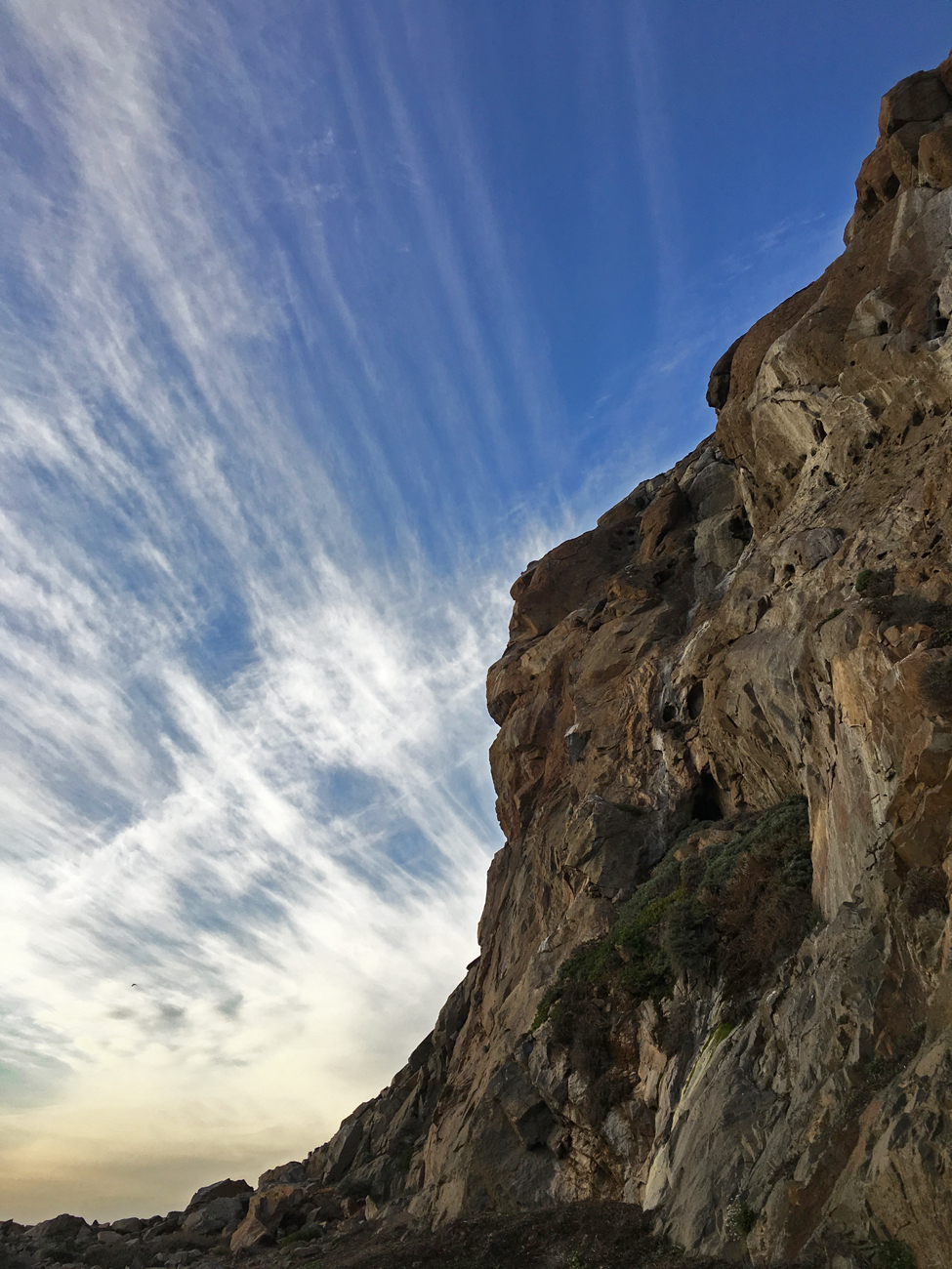 Part of Morro Rock against the sky with wispy clouds reflecting the sun
