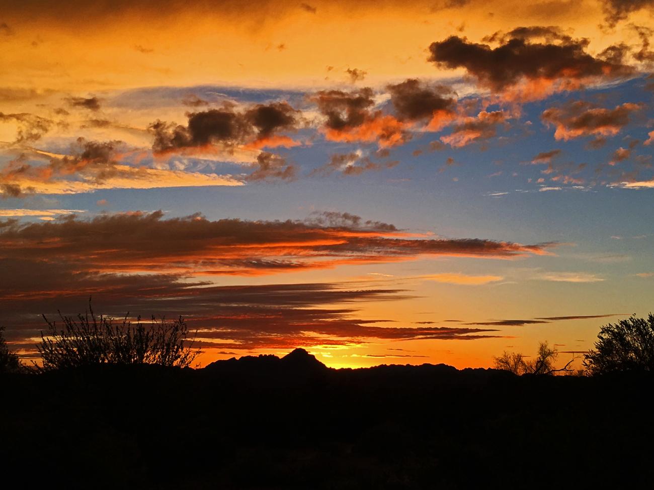 Dramatic, intense red and orange sunset behind the Trigo Mountains