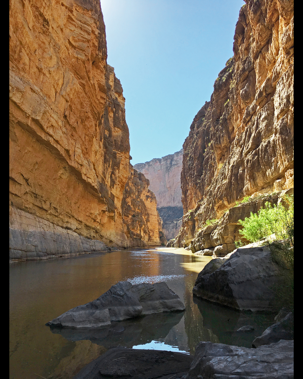 View inside Santa Elena Canyon from the river's edge with warm brown canyon walls and a boulder in the river